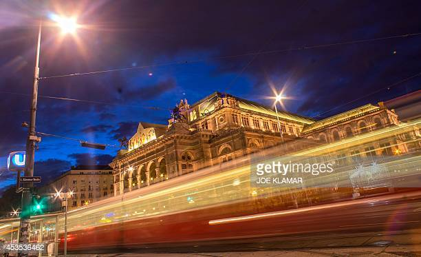A city tram passes by the litup Wiener Staatsoper Vienna's State Operaduring the twilight in the city center of Vienna on August 122014The Vienna...