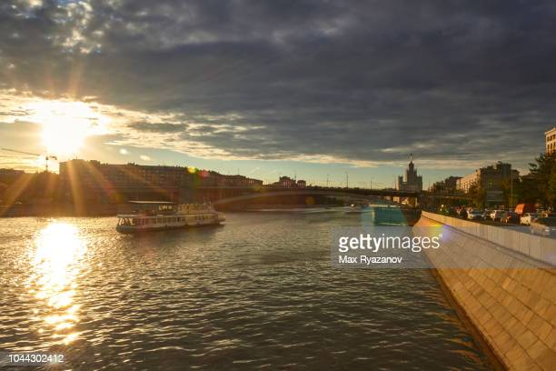 City view of Moscow with the river in the foreground and residential buildings in the background. The sun comes out of the storm clouds