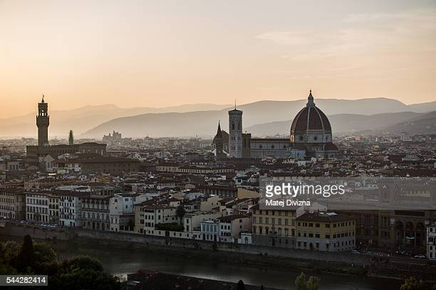 A city view with the Santa Maria del Fiore Cathedral also known as the Duomo right Giotto's Campanile and the Palazzo Vecchio left during sunset is...