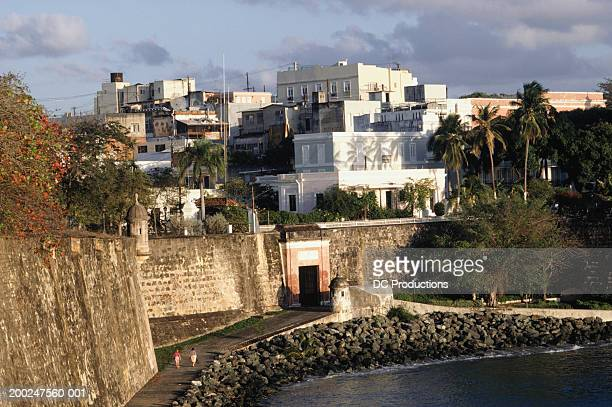 city wall and buildings in old san juan, puerto rico - old san juan wall stock photos and pictures
