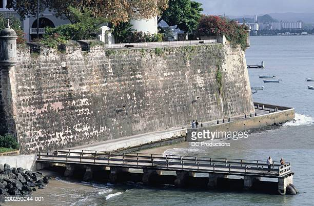 city wall and pier, old san juan, puerto rico - old san juan wall stock photos and pictures