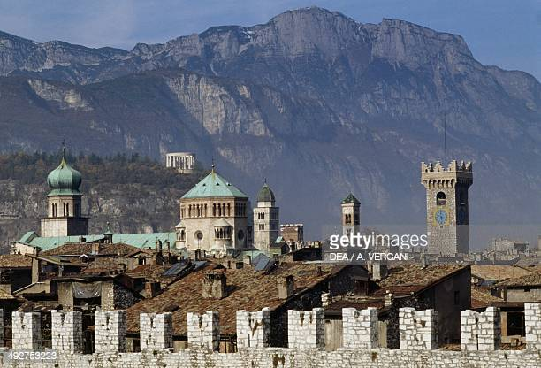 City walls in Piazza della Fiera in the foreground with the towers of Trento Cathedral and the Mausoleum of Cesare Battisti in the background Trento...