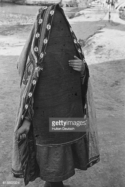 A city woman wears a long horsehair veil and embroidered coat hung from her head
