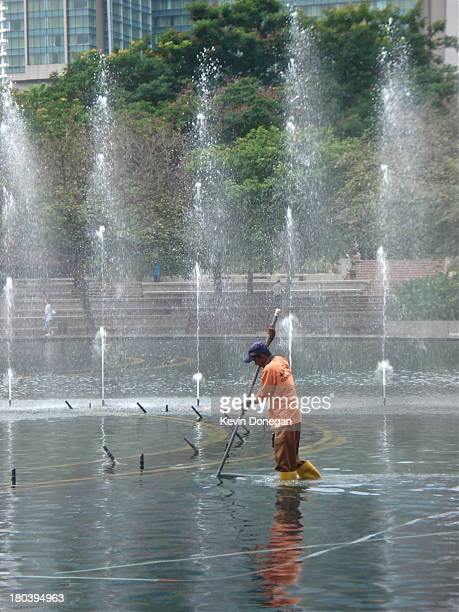 City worker cleans fountain in downtown Kuala Lumpur.