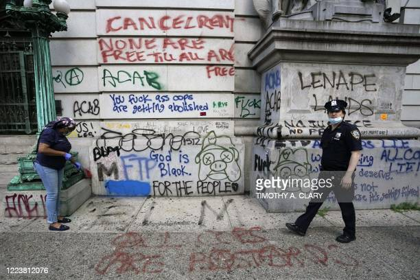 City worker cleans up the street in front of a New York City government building on July 1, 2020 across the street from the Black Lives Matter...