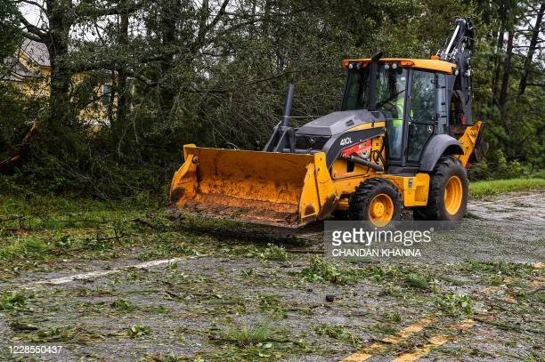 A city worker clears fallen trees during Hurricane Sally landfall on the outskirts of Mobile Alabama on September 16 2020 Hurricane Sally barrelled...
