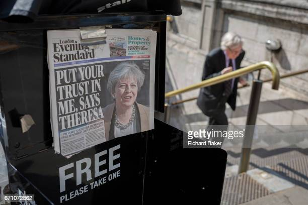 A City worker climbs steps at Bank Underground station past Evening Standards with Prime Minister Theresa May on the front page asking the nation to...