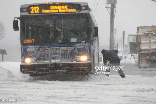 A city worker digs out a bus from the snow on January 4 2018 in New Haven Connecticut The bomb cyclone was expected to dump heavy snows in New...