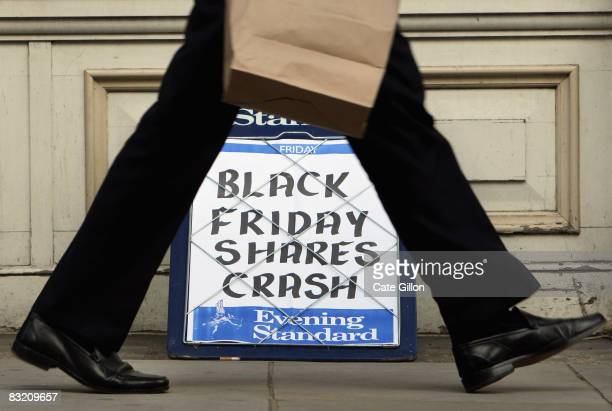 A city worker passes the Evening Standard headline board showing the words 'Black Friday Shares Crash' during lunch time on Friday on October 10 2008...