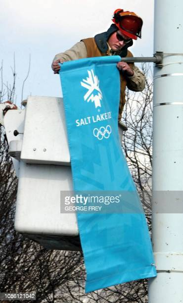 City worker Paul Brown installs Olympic banners on light poles near the Peaks Ice Arena site of women's ice hocky for the 2002 Winter Olympics 30...