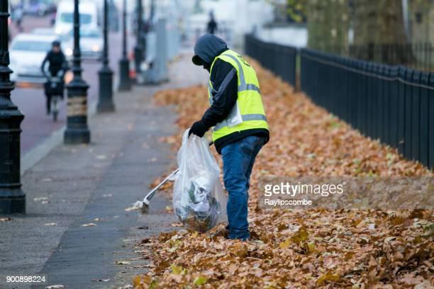 Trabajador de la ciudad levantando basura rodeado de otoño las hojas, cerca del Palacio de Buckingham, Londres