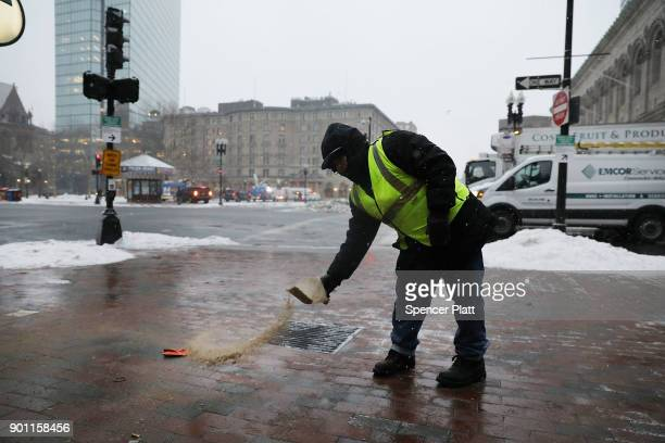City worker puts down salt along the empty streets of Boston as the snow begins to fall during a massive winter storm on January 4, 2018 in Boston,...