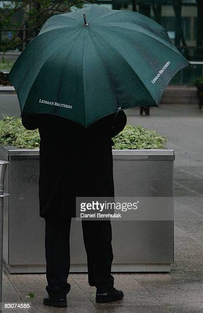 A city worker shelters under a Lehman Brothers umbrella as he stands outside of the Lehman Brothers headquarters in Canary Wharf on October 1 2008 in...