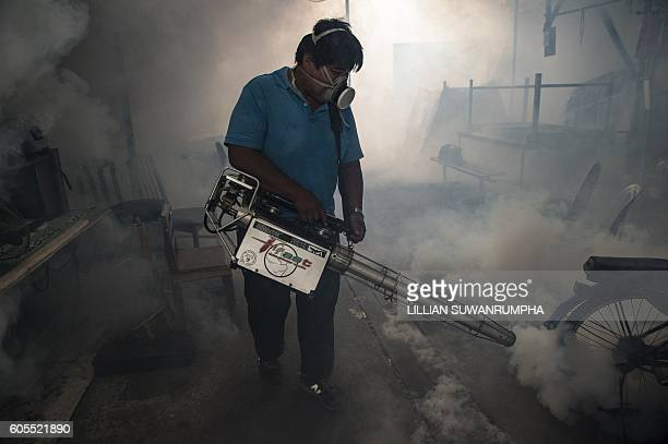 A city worker sprays chemicals with a fumigator to kill mosquitoes in an effort to control the spread of the Zika virus at a school in Bangkok on...