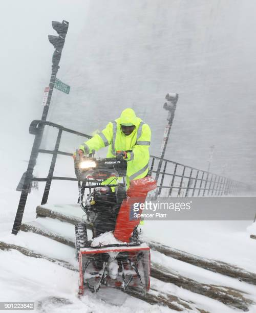 A city worker struggles with a snow blower on the streets of Boston as snow falls from a massive winter storm on January 4 2018 in Boston United...
