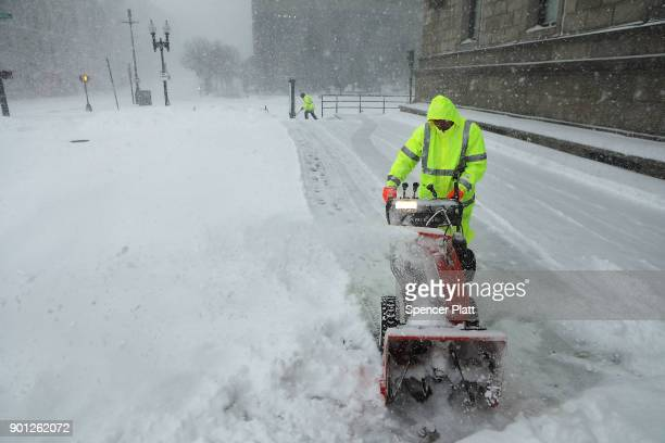 A city worker uses a snow blower to clear sidewalks as snow falls from a massive winter storm on January 4 2018 in Boston United States Schools and...