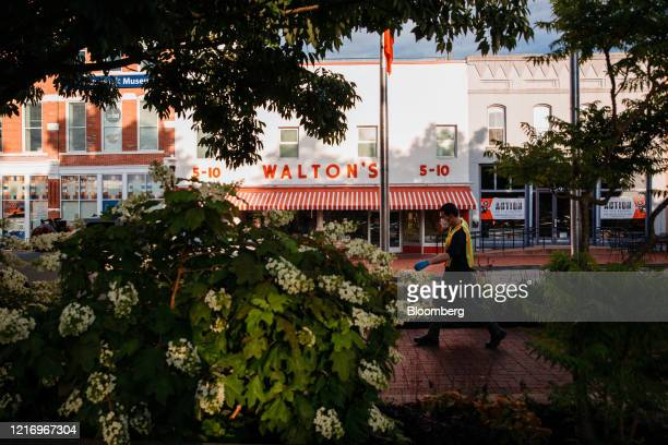 A city worker wears a protective mask and gloves while passing in front of the Walmart Museum's Walton's 5 10 in Bentonville Arkansas US on Thursday...