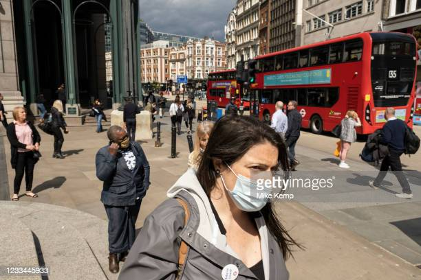 City workers, and commuters, many of whom are wearing face masks heading towards the entrance to Liverpool Street Station on Bishopsgate on 26th May...