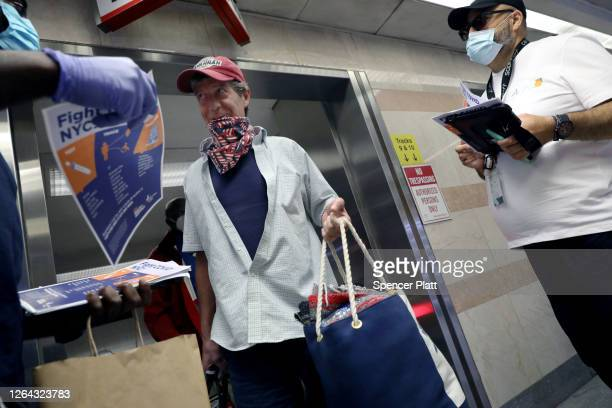 City workers attempt to hand out information sheets to travelers arriving by train to Pennsylvania Station from states affected by rules requiring...