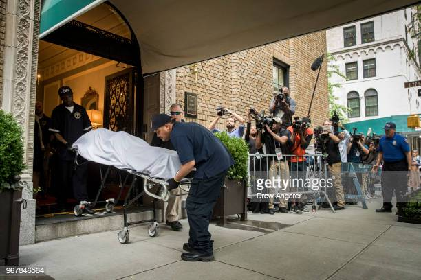 City workers carry the body of fashion designer Kate Spade out of her apartment building after she was found dead of an apparent suicide on June 5...