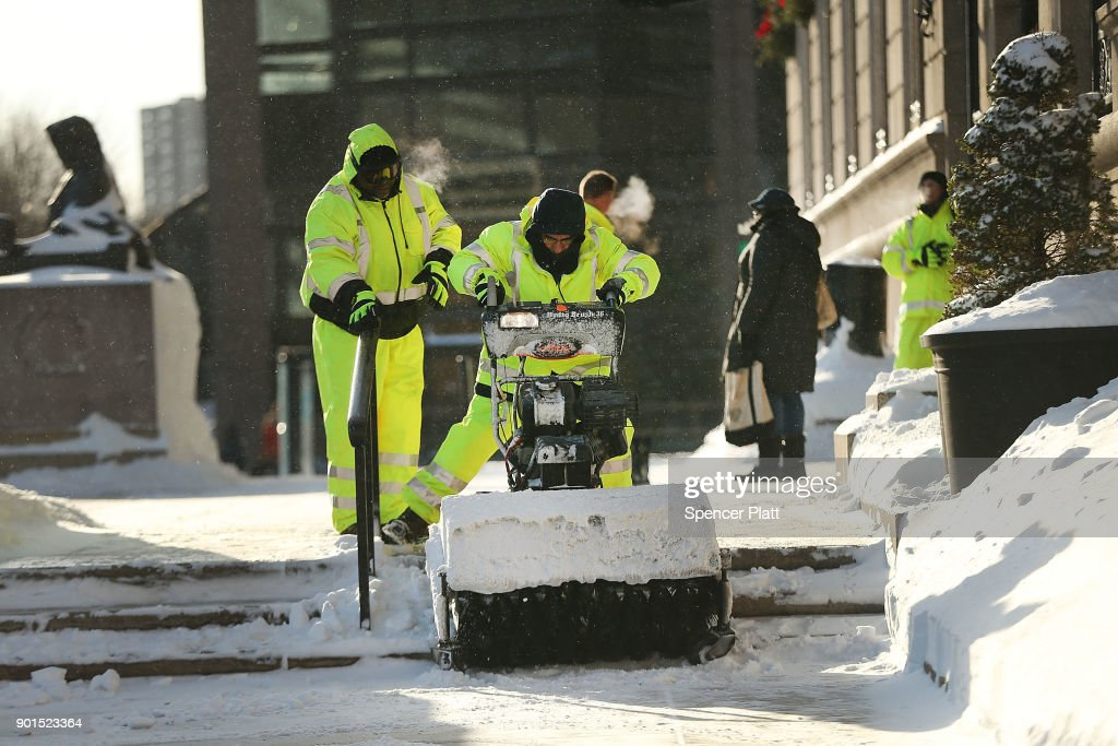 City workers clear snow the morning after a massive winter storm on January 5, 2018 in Boston, Massachusetts. Schools and businesses throughout the Boston area get back to work today after the city received over a foot of snow during a fast moving storm yesterday.