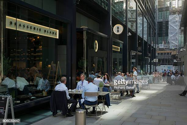 City workers eat lunch outside at Brasserie Blanc during an unusual autumn heatwave on 13th September 2016 in the City of London England
