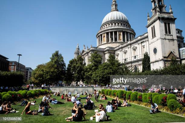 City workers eat their lunches in front of St Paul's Cathedral during the sweltering lunchtime break in the City of London on August 6 2018 in London...