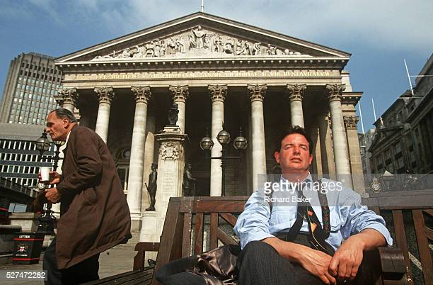 City workers enjoy a lunchtime siesta in summer sunshine under solid Corinthian pillars of the Royal Exchange in City of London With his tie askew...