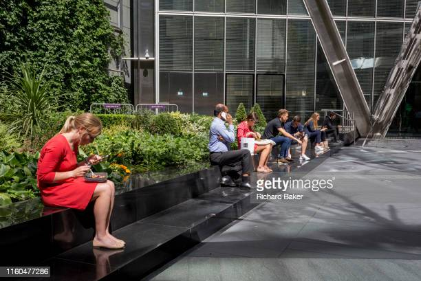 City workers enjoy their lunches in summer sunshine on Primrose Street in the City of London the capital's financial district aka the Square Mile on...