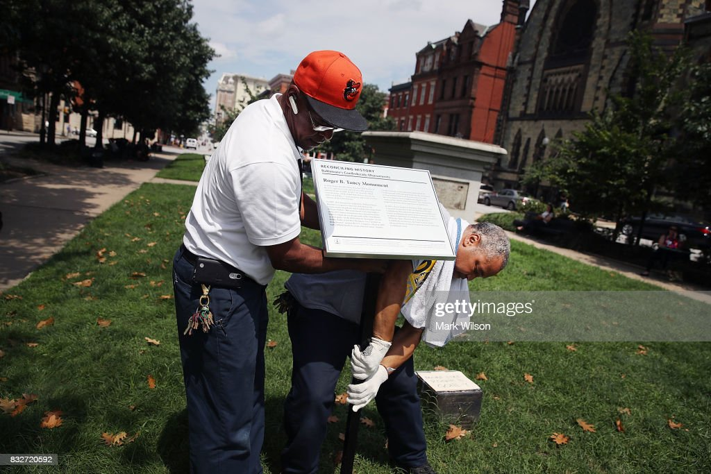 City workers remove a plaque near the pedestal that was formerly the base for a statue of Roger B. Taney, former Chief Justice of the U.S. Supreme Court and majority author of the Dred Scott decision, August 16, 2017 in Baltimore, Maryland. The City of Baltimore removed four statues celebrating confederate figures from city parks overnight, following the weekend's violence in Charlottesville, Virginia.