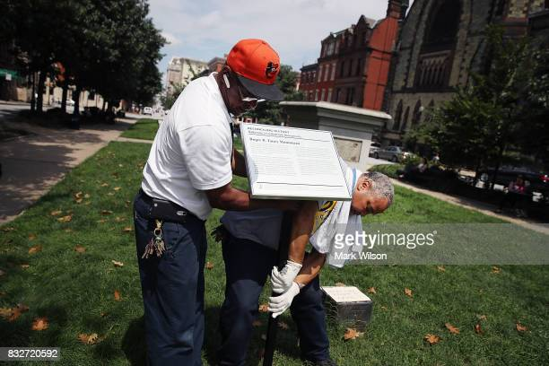 City workers remove a plaque near the pedestal that was formerly the base for a statue of Roger B Taney former Chief Justice of the US Supreme Court...
