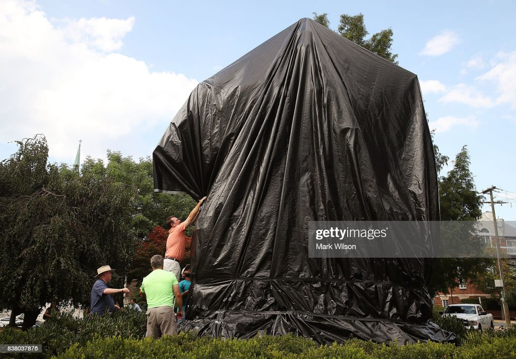 City workers repair the black sheet that was put over the statue of Confederate Gen. Robert E. Lee, after a man tried to take cut it off, on August 23, 2017 in Charlottesville, Virginia. Earlier this week the Charlottesville city council voted unanimously to cover Confederate statues in black cloth.