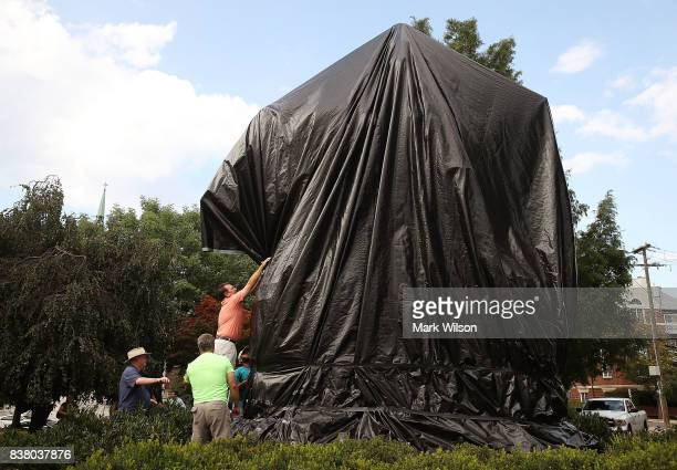 City workers repair the black sheet that was put over the statue of Confederate Gen Robert E Lee after a man tried to take cut it off on August 23...