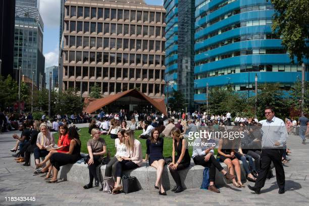 City workers take a break at lunchtime in the now redeveloped area with modern glass offices and angular structures at Aldgate in the City of London...
