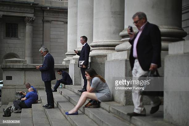 City workers talk on their mobile phones near the Bank of England as the financial markets face uncertainty in the wake of Brexit on June 27 2016 in...