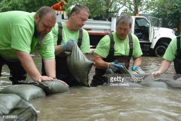 City workers use sandbags to fight rising floodwaters from sewers on June 12, 2008 in Cedar Rapids, Iowa. Much of the city has been evacuated as the...