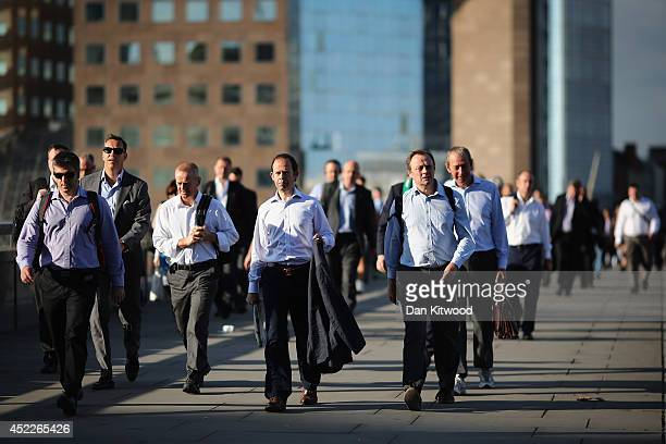 City Workers walk along London Bridge in the early morning sunshine on July 17 2014 in London England The Met Office has issued a heatwave alert as...