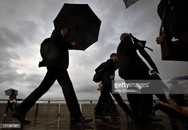 City workers walk over London Bridge in central London on August 18 2011 London's main stock index slumped by more than 50 percent in Thursday...