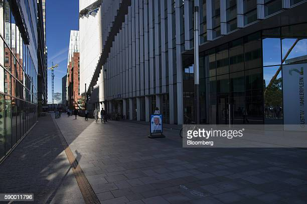 City workers walk past offices on their way to work in the Zuidas business district of Amsterdam Netherlands on Monday Aug 15 2016 The Dutch city a...
