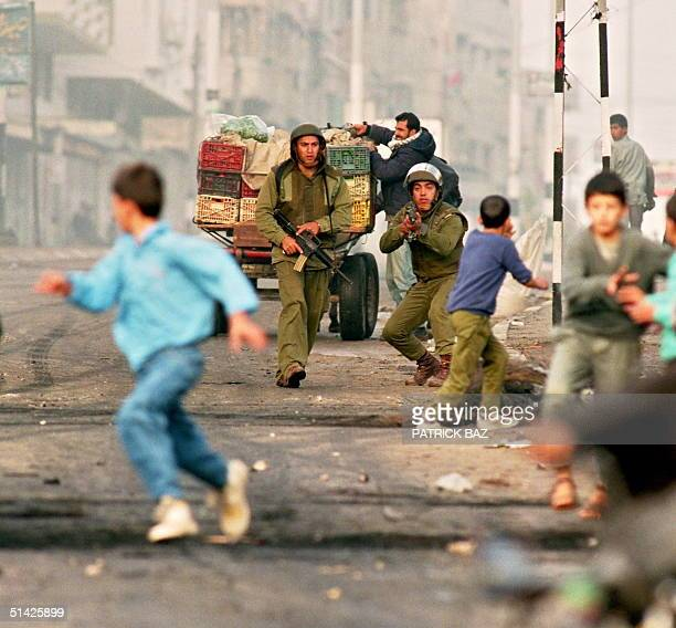 Palestinian youngsters flee Israeli soldiers during riots 26 November 1993 in Gaza City The Palestinian uprising intifada against Israeli occupation...