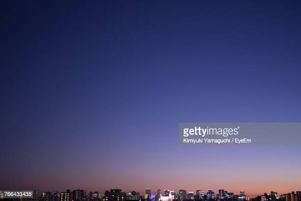 Cityscape Against Clear Blue Sky At Night