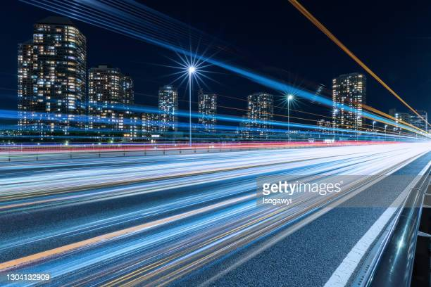cityscape against clear sky and light trails at night - isogawyi stock pictures, royalty-free photos & images