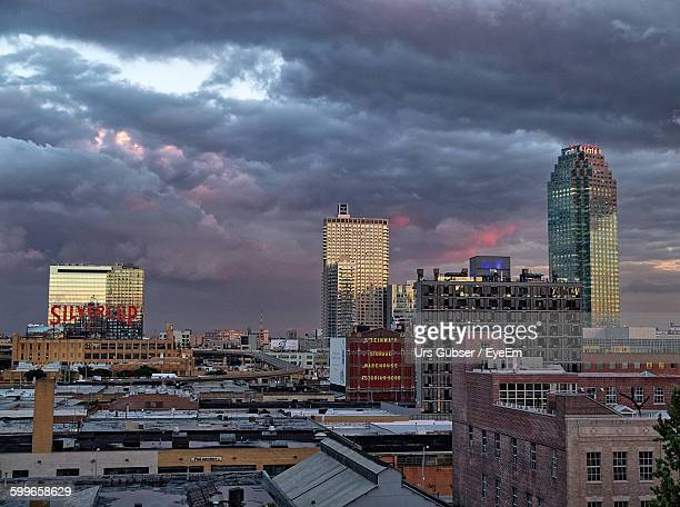 cityscape against cloudy sky - long island city stock photos and pictures