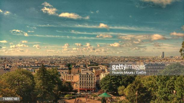 cityscape against cloudy sky - moura stock photos and pictures