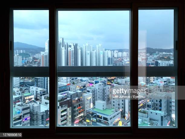 cityscape against sky seen through glass window - south korea stock pictures, royalty-free photos & images