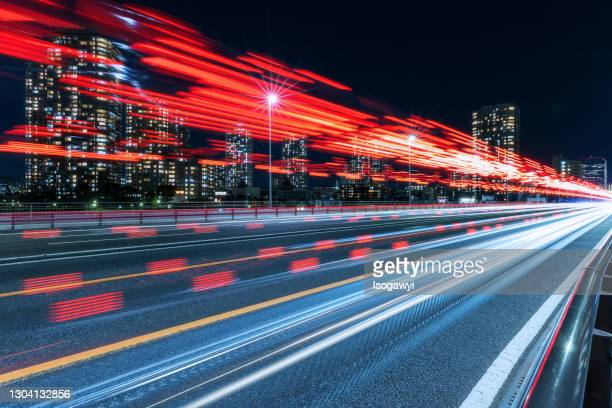cityscape and red light trails at night - isogawyi bildbanksfoton och bilder