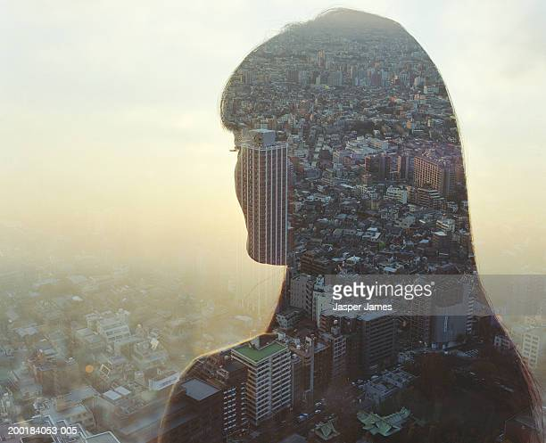 Cityscape and young woman, rear view (double exposure)