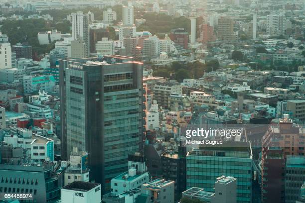 A cityscape at dusk in Tokyo, Japan is seen in abstract colors of blue, orange and teal.