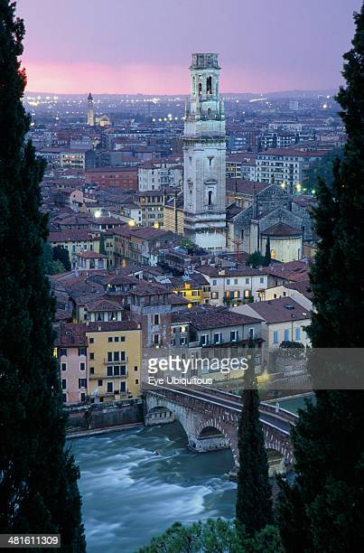 Cityscape at sunset showing tiled rooftops Duomo bell tower and bridge over the Adige River