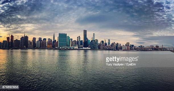 Cityscape By East River Against Cloudy Sky